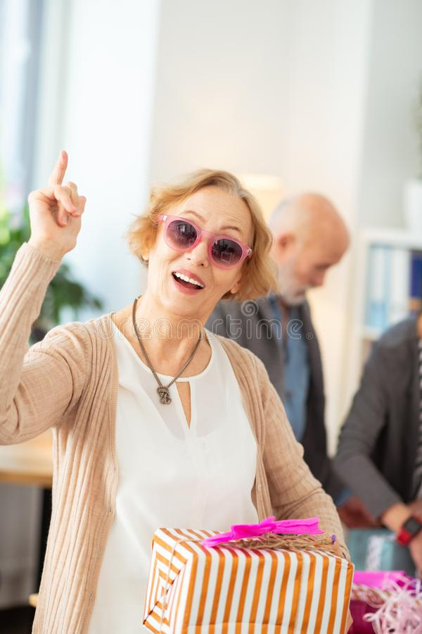 Mulher feliz agradável que aponta acima com seu dedo imagem de stock