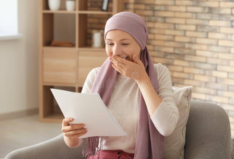 Mulher feliz após resultados da análise da leitura da quimioterapia em casa imagem de stock royalty free