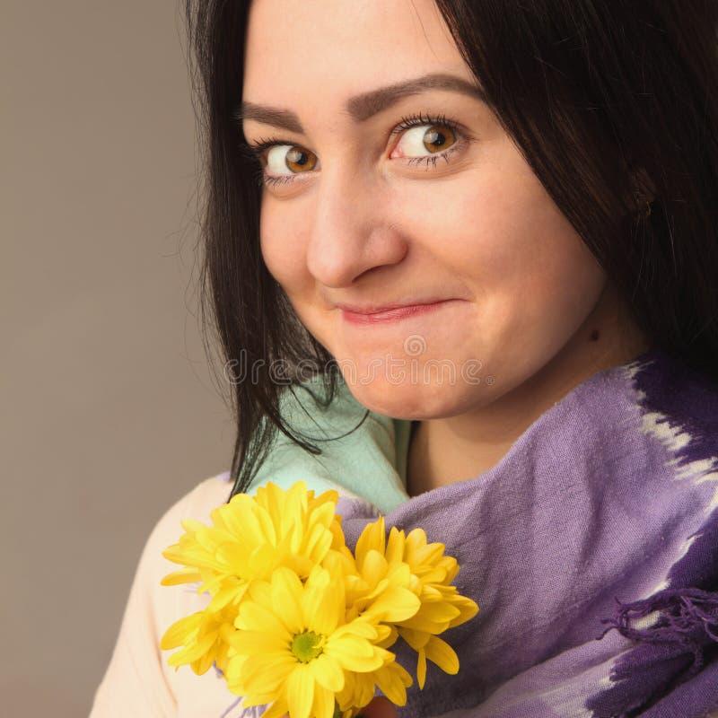 Mulher feliz atrativa do retrato que guarda flores imagem de stock