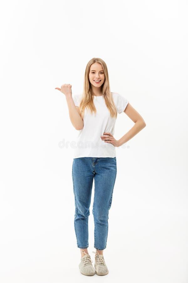 Mulher feliz atrativa nova no pano ocasional que aponta no fundo branco do espaço da cópia imagem de stock royalty free