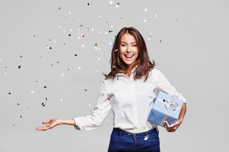 Mulher feliz bonita com a caixa de presente no partido da celebração com os confetes que caem em toda parte nela fotografia de stock