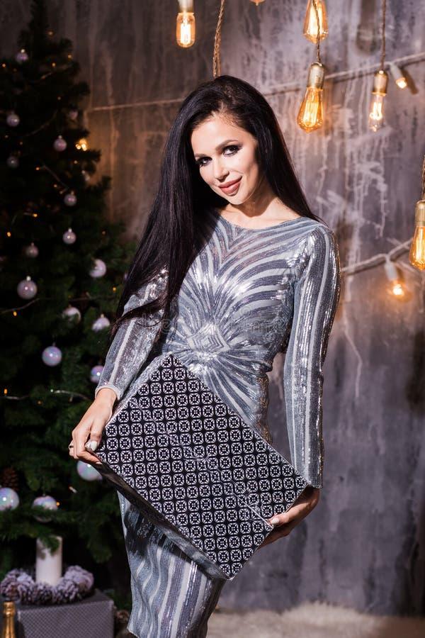 Mulher feliz bonita com a caixa de presente no partido da celebração com os confetes que caem em toda parte nela Véspera do anive imagens de stock royalty free