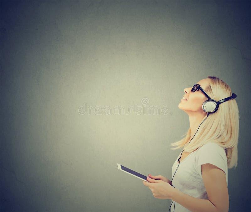 Mulher feliz bonita com fones de ouvido que escuta a música na tabuleta fotografia de stock