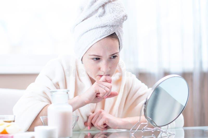 Mulher feliz bonita com uma toalha em sua cabeça que olha sua pele em um espelho Conceito da higiene e do cuidado para a pele foto de stock