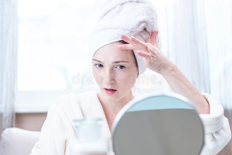 Mulher feliz bonita com uma toalha em sua cabeça que olha sua pele em um espelho Higiene e cuidado para a pele fotos de stock royalty free