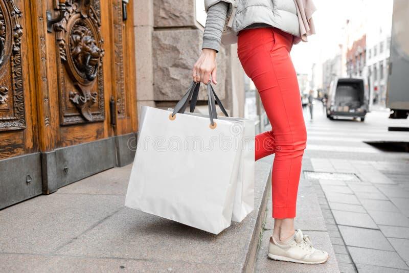 A mulher feliz bonita de Shopaholic vai comprar na cidade Moça em calças vermelhas e em muitos sacos de papel cinzentos ela fotografia de stock royalty free