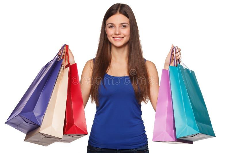 Mulher feliz bonita de sorriso que guarda os sacos de compras, venda, no fundo branco foto de stock royalty free