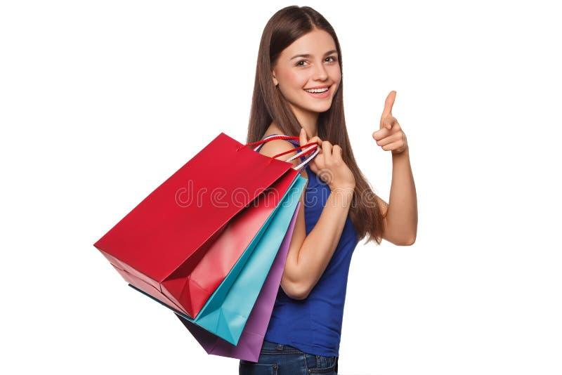 Mulher feliz bonita do sorriso que guarda os sacos de compras, isolados no fundo branco fotos de stock
