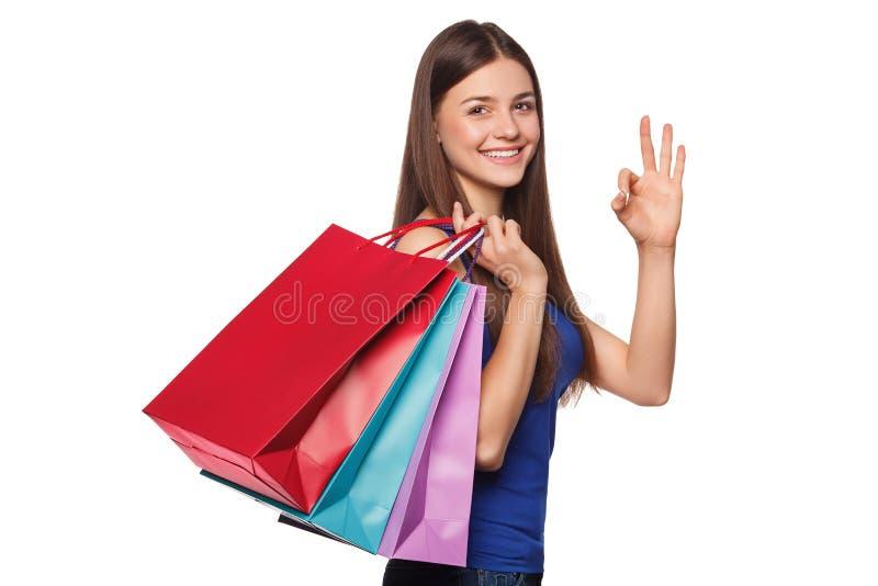 Mulher feliz bonita do sorriso que guarda sacos de compras e que mostra o sinal aprovado, isolado no fundo branco fotos de stock