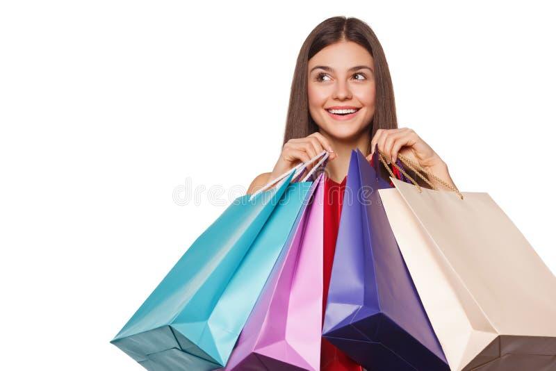 Mulher feliz bonita do sorriso que guarda sacos de compras, venda, isolada no fundo branco imagens de stock
