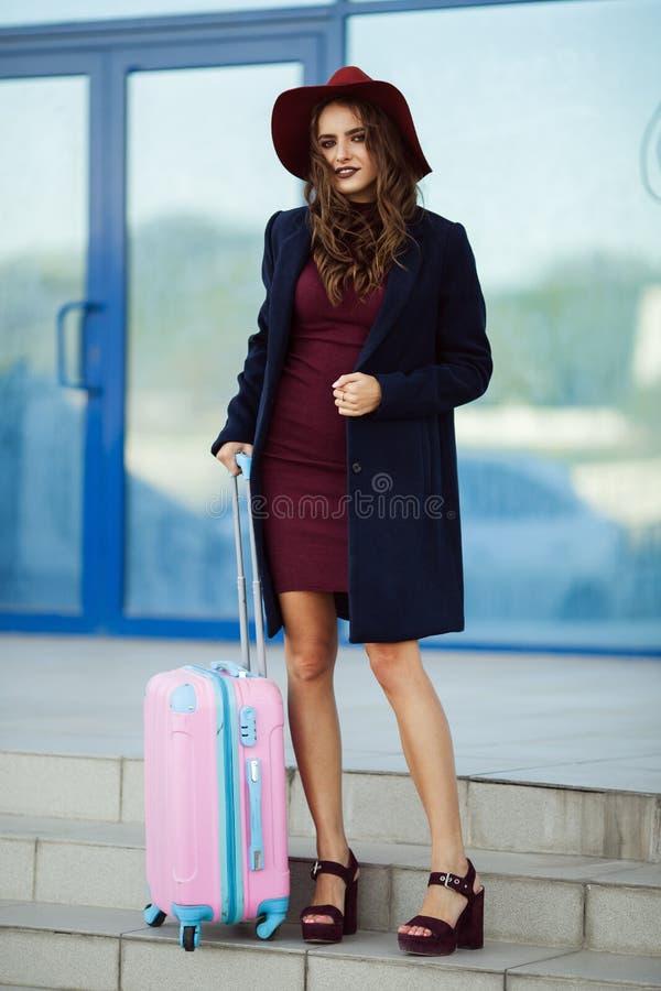 A mulher feliz bonita está vestindo a roupa e o chapéu da forma perto da construção do aeroporto com mala de viagem cor-de-rosa c fotos de stock
