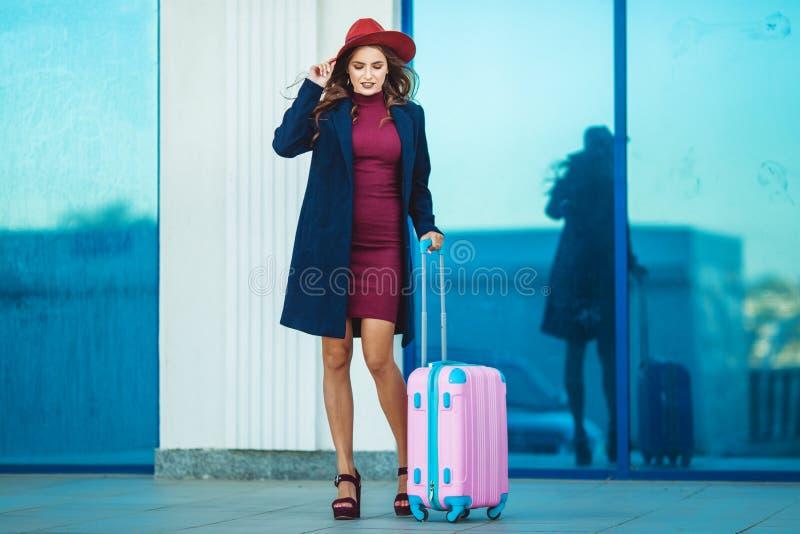 A mulher feliz bonita está vestindo a roupa e o chapéu da forma perto da construção do aeroporto com mala de viagem cor-de-rosa F fotos de stock