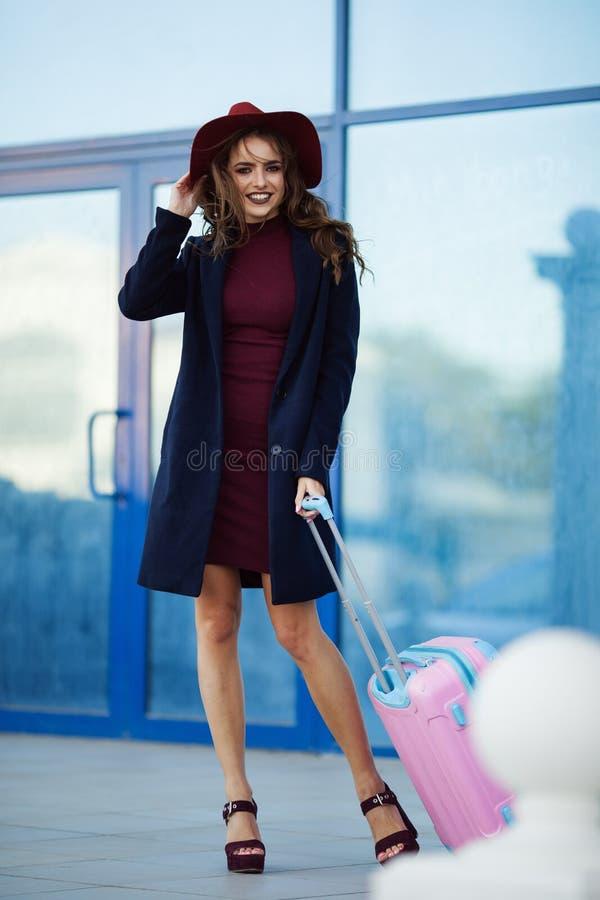 A mulher feliz bonita está vestindo a roupa e o chapéu da forma perto da construção do aeroporto com mala de viagem cor-de-rosa F imagens de stock