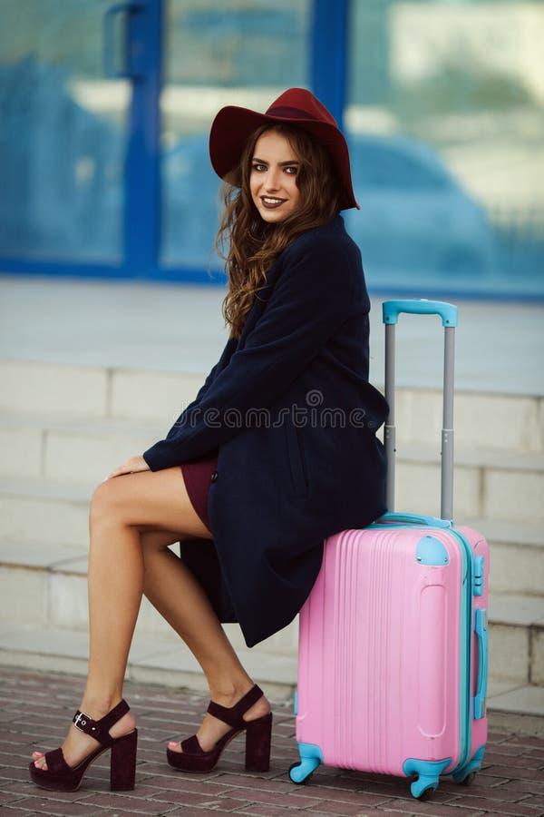 A mulher feliz bonita está vestindo a roupa e o chapéu da forma perto da construção do aeroporto que senta-se na mala de viagem c fotos de stock