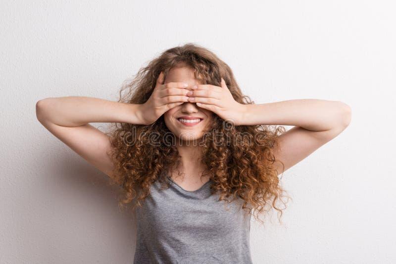 Mulher feliz bonita nova no estúdio, cobrindo seus olhos fotos de stock