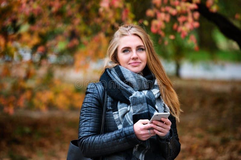 Mulher feliz bonita que anda e que texting no parque do outono imagem de stock