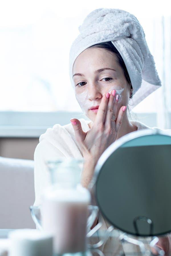 Mulher feliz bonita que aplica o creme na cara que hidrata a pele Higiene e cuidado para a pele em casa imagem de stock
