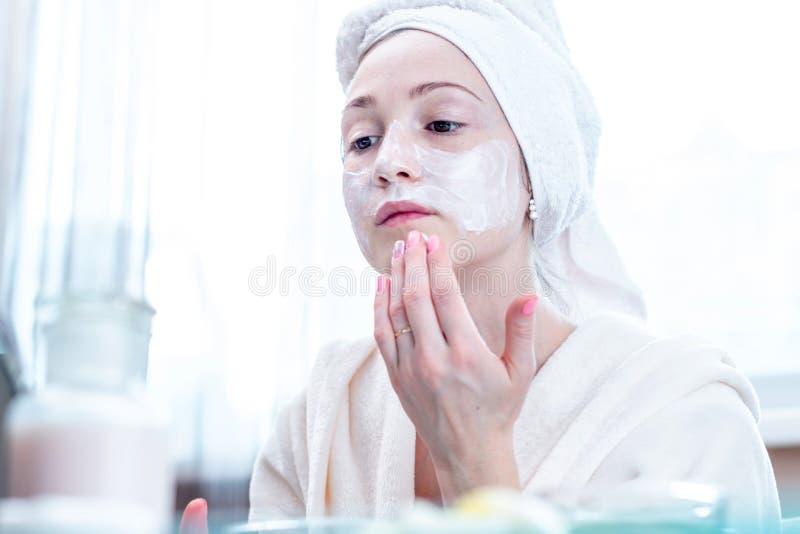 Mulher feliz bonita que aplica o creme na cara que hidrata a pele Higiene e cuidado para a pele em casa fotos de stock