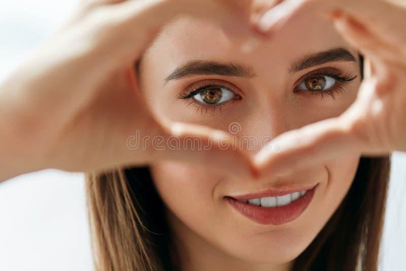 Mulher feliz bonita que mostra o sinal do amor perto dos olhos foto de stock