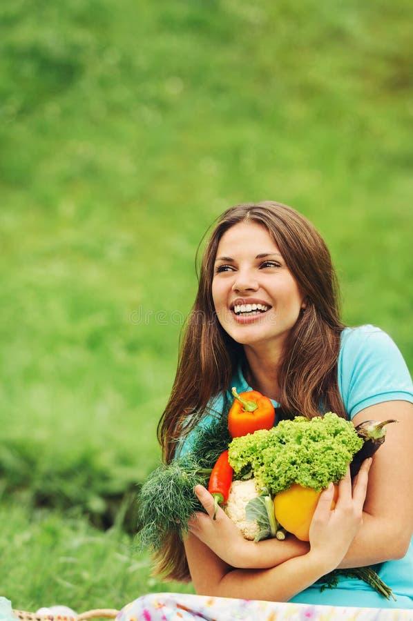 Mulher feliz bonito com os vegetais saudáveis orgânicos imagem de stock