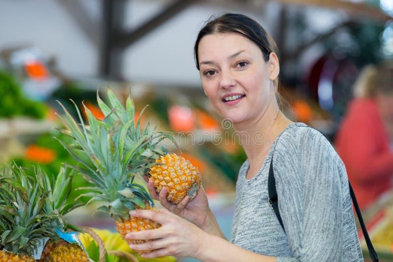 Mulher feliz com abacaxi no supermercado imagem de stock