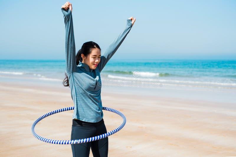 Mulher feliz com a aro do hula na praia imagens de stock royalty free