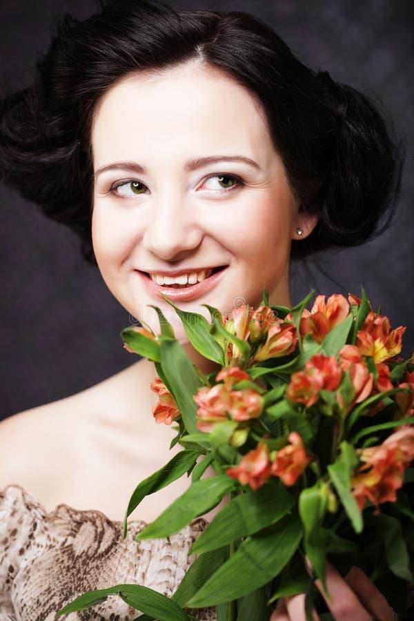 Mulher feliz com as flores nas mãos A moça atrativa nova guarda o ramalhete de flores vermelhas e amarelas fotografia de stock