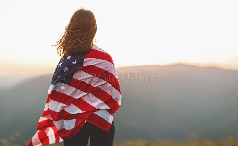 Mulher feliz com a bandeira de Estados Unidos que aprecia o por do sol no na fotografia de stock