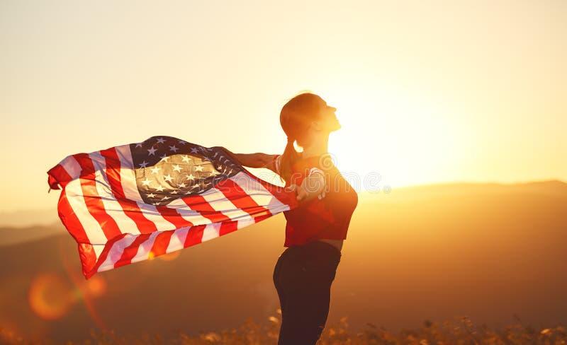 Mulher feliz com a bandeira de Estados Unidos que aprecia o por do sol no na imagens de stock