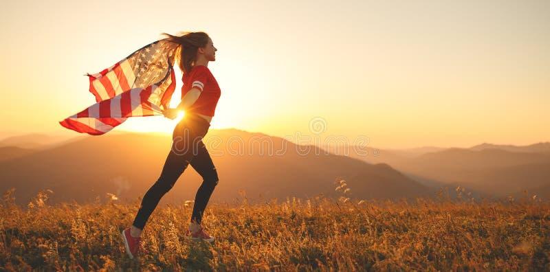 Mulher feliz com a bandeira de Estados Unidos que aprecia o por do sol no na fotos de stock