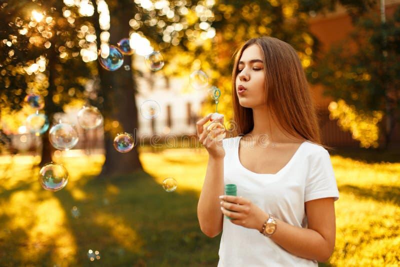 Mulher feliz com bolhas de sabão de sopro do humor do verão no parque fotografia de stock