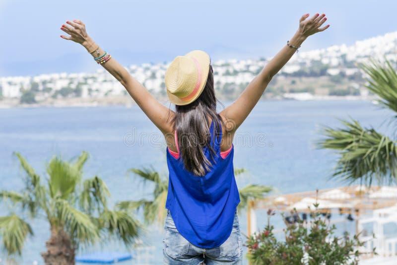 Mulher feliz com braços abertos que olha o mar Férias de verão foto de stock royalty free