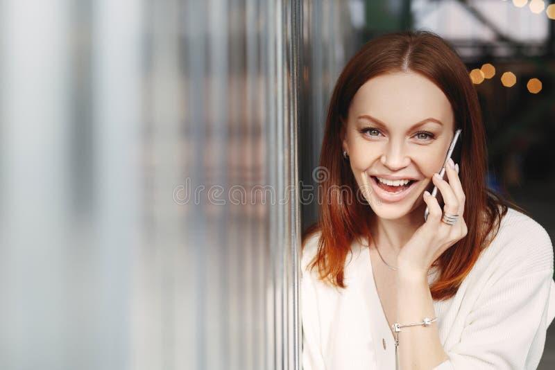 A mulher feliz com cabelo tingido, obtém a boa notícia durante a conversação no telefone celular, discute a notícia a mais atrasa imagens de stock