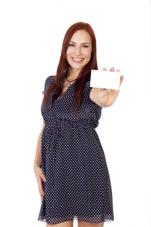 A mulher feliz com cabelo vermelho guarda para fora um cartão vazio. imagem de stock