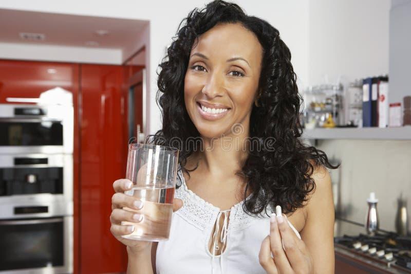 Mulher feliz com comprimido e vidro da água imagem de stock royalty free