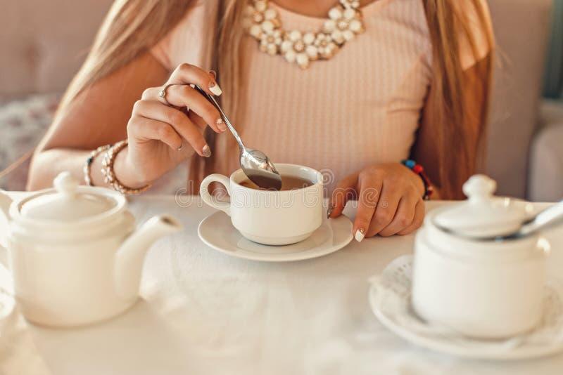 Mulher feliz com copo de chá As mãos guardam uma colher de chá Louça branca na aba foto de stock royalty free