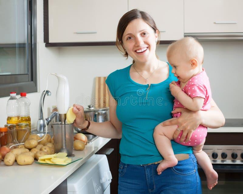 Mulher feliz com a criança que cozinha batatas trituradas foto de stock