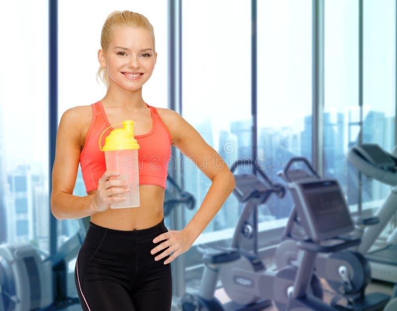 Mulher feliz com a garrafa da agitação da proteína no gym foto de stock royalty free