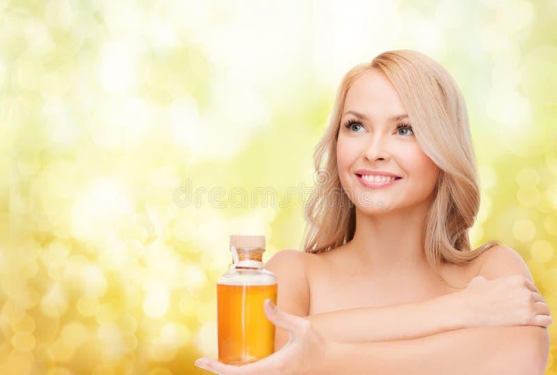 Mulher feliz com garrafa de óleo fotografia de stock