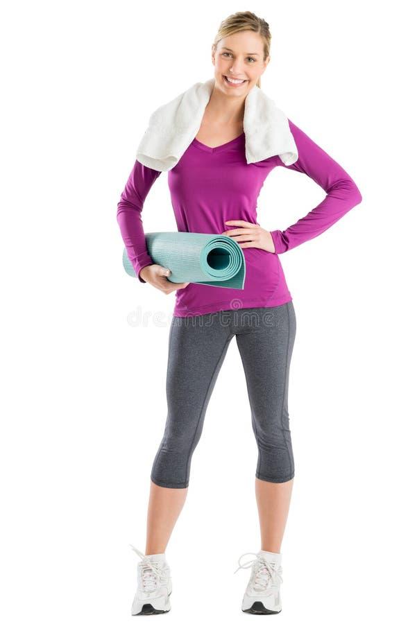 Mulher feliz com mão no quadril ao guardar a esteira do exercício imagem de stock