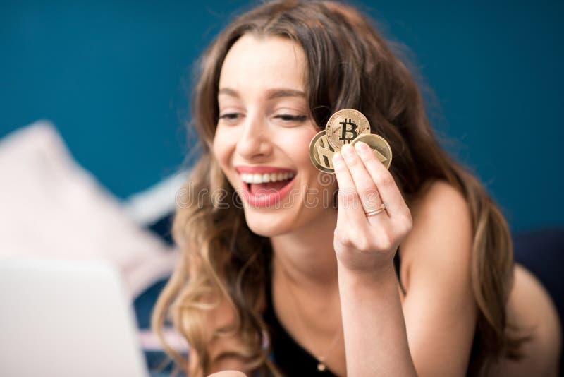 Mulher feliz com moeda cripto em casa fotos de stock