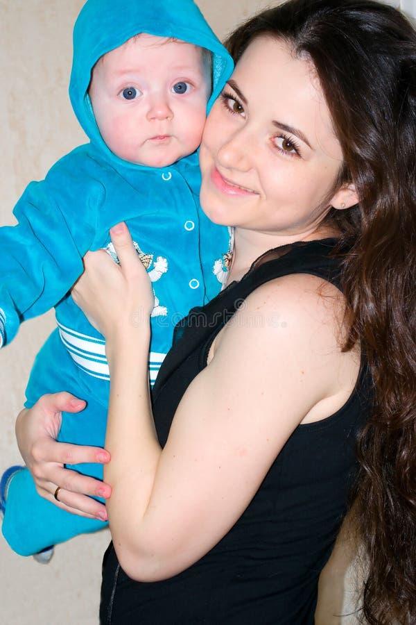 Mulher feliz com o bebê pequeno que sorri e que joga jogos imagem de stock