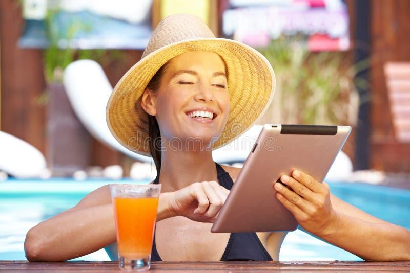 Mulher feliz com o computador da tabuleta na associação fotografia de stock royalty free