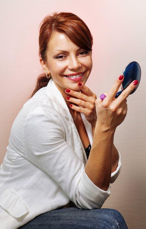 Mulher feliz com o espelho compacto azul fotografia de stock