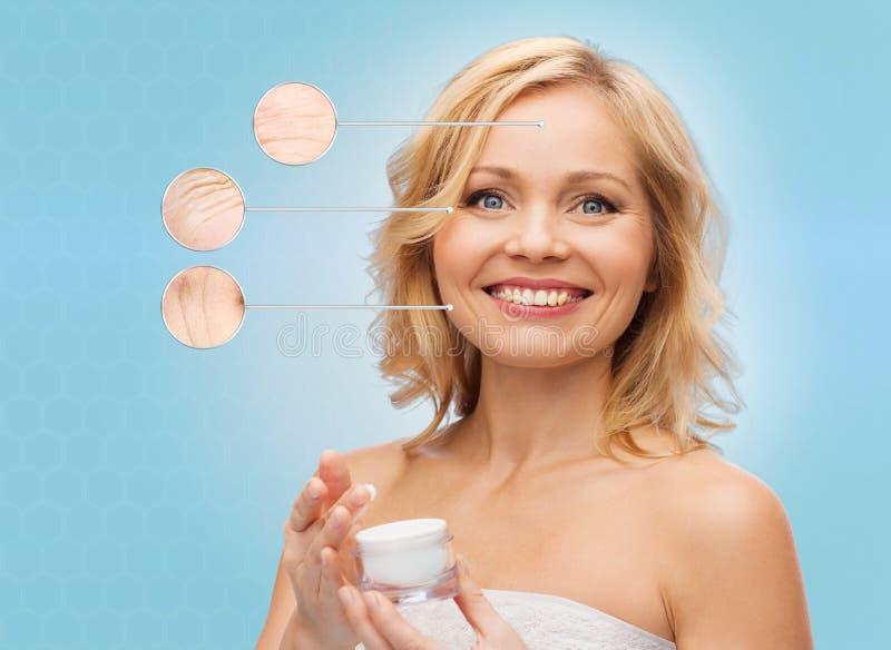 Mulher feliz com o frasco de creme antienvelhecimento fotografia de stock