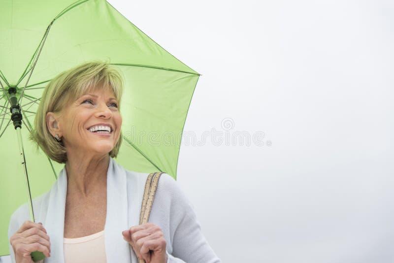 Mulher feliz com o guarda-chuva verde contra o céu claro foto de stock royalty free