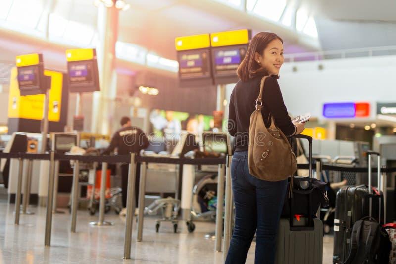 Mulher feliz com o passaporte da terra arrendada da mão do sorriso e a passagem de embarque foto de stock royalty free