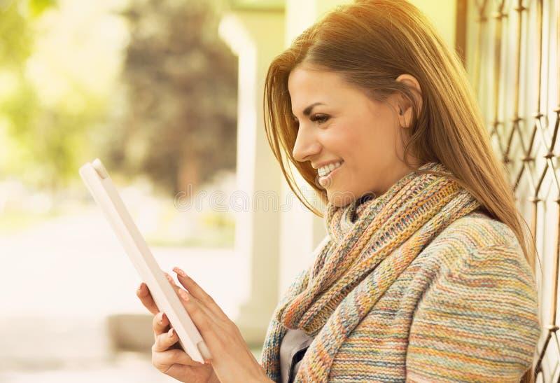 Mulher feliz com o tablet pc que está fora em uma rua da cidade em um dia de verão fotos de stock