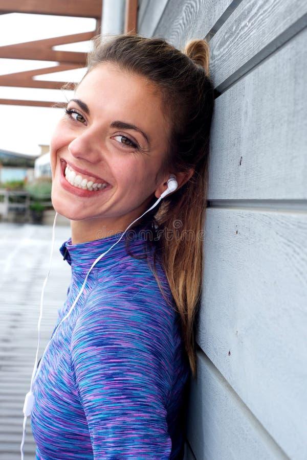 Mulher feliz com os fones de ouvido que estão fora imagem de stock royalty free