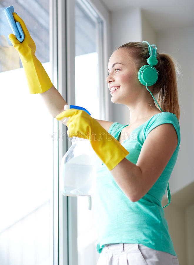 Mulher feliz com os fones de ouvido que limpam a janela imagem de stock